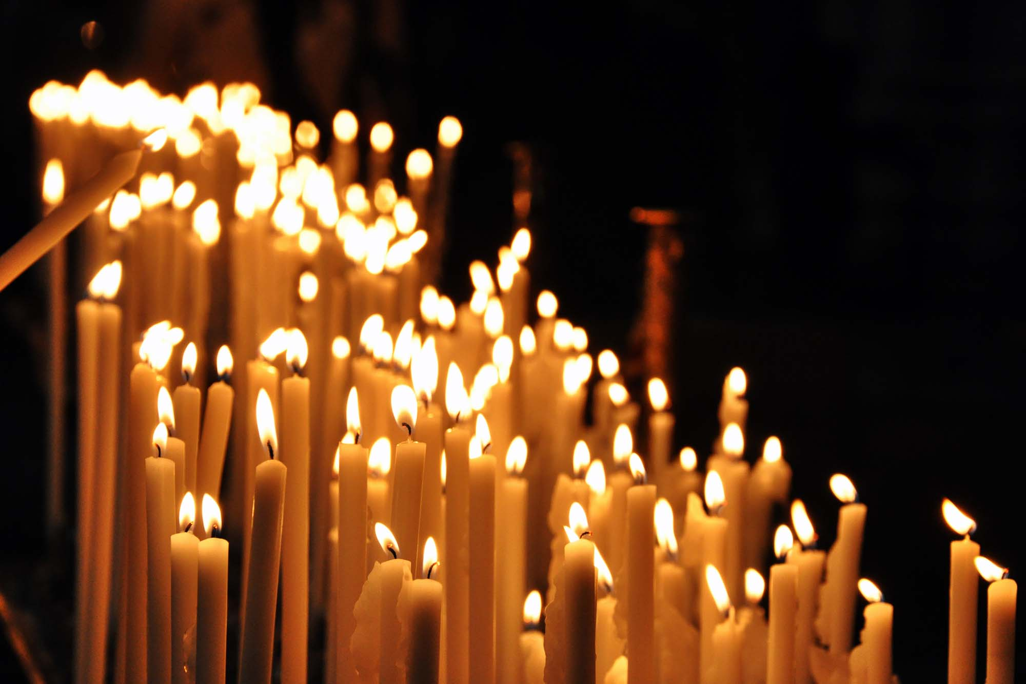 Church candles being lit for prayer