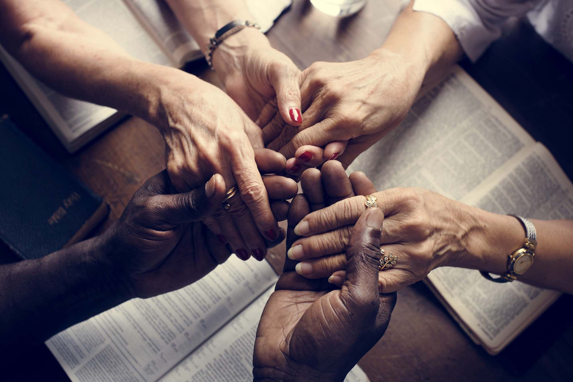 Hands linking up in prayer around a table